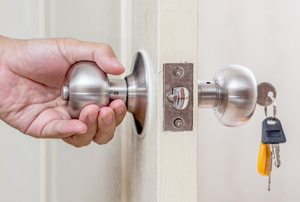 A hand opening a door knob with keys in it.