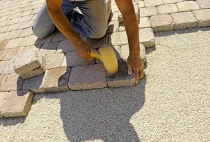 man installing stone pavers