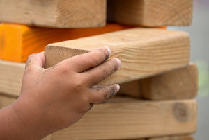 A child's hand playing with an oversized Jenga game.