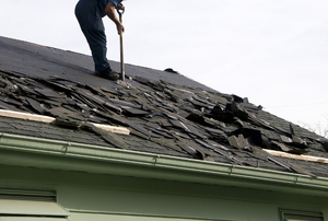A construction worker removing shingles from a roof.