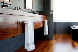 bathroom with wood cabinets and floors