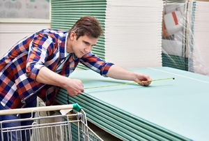 A handyman in a plaid shirt measuring drywall in a home improvement store.