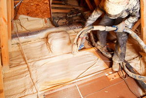 A worker installing blown-in insulating in an unfinished floor.