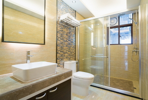 bathroom with glass shower, white sink and dark cabinets