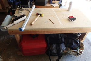 Several tools sit on a wooden workbench.