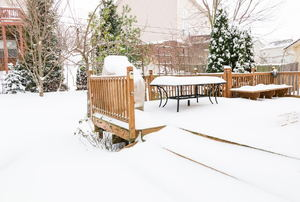 A snow-covered deck in a yard.