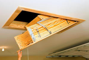 A hand pulling down a set of stairs to a storage area above an attic.