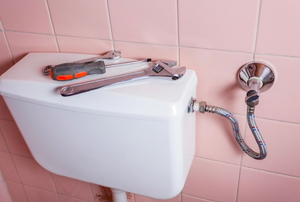 a toilet tank with tools on top