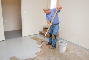 A DIYer painting a garage floor.