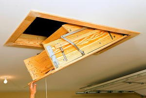 A hand pulling down an access ladder from a garage ceiling.