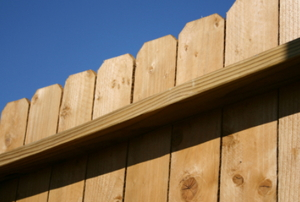 A top wooden rail and the fence boards on a wood fence.