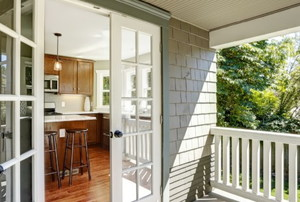 double doors leading into a wood-floored kitchen from a sunny porch
