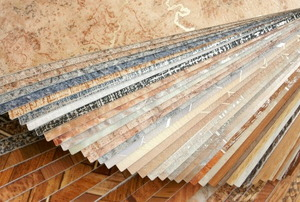 A stack of many different designs of vinyl flooring tiles.