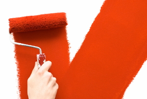 A paint roller applying paint to a wall.