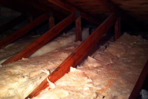 Fiberglass insulation on an attic floor, between the joists.