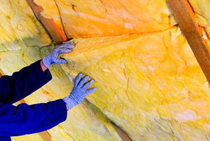 Blue-gloved hands installed a roll of yellow, foam insulation in an attic wall.