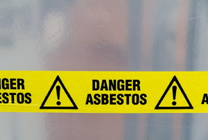 "Yellow tape with the words ""danger asbestos"" on it."