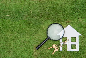 A paper house on grass with a magnifying glass and a set of house keys.
