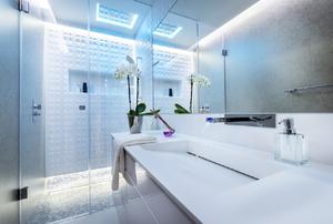 A modern bathroom with frameless, glass shower doors.