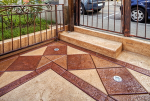 A beige and brown stamped concrete patio surrounded by a metal fence.