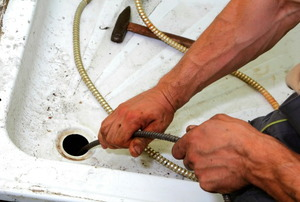 Snaking out a clogged shower drain.