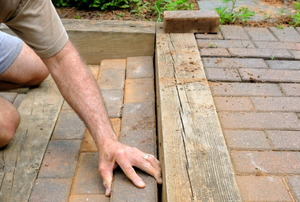 Laying brick patio pavers in the backyard.