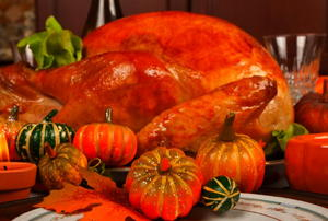 A Thanksgiving turkey with decorative mini-pumpkins in the foreground.