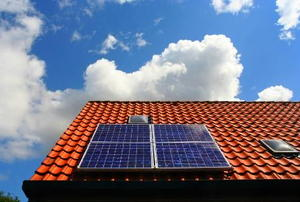 A blue solar panel on a red stucco roof with clouds in the background.