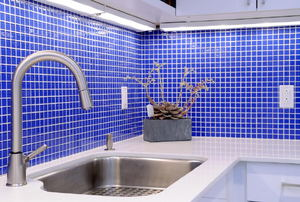 kitchen counter with walls of small blue tile backsplash