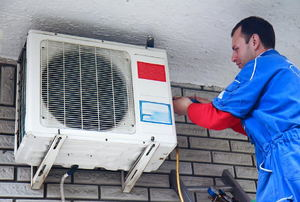 Man on a ladder repairing an air conditioner