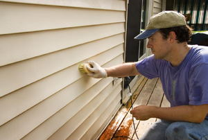 A man works on siding.