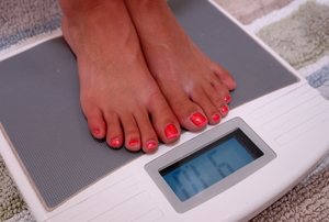 A person standing on a digital scale to measure their weight.