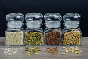 A row of seeds in 4 glass jars.