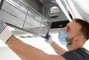 person removing dusty air filter from large vent