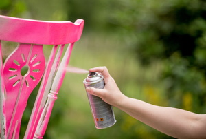 A chair being spray painted pink.