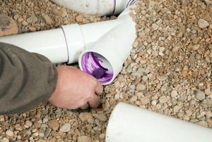 A hand applying purple PVC cement to the inside of a pipe.