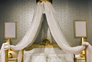 Bed with gold frame and cream canopy and bed cover