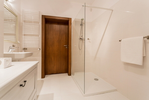 A standing shower with a glass enclosure.