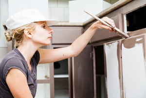 A woman painting kitchen cabinets.