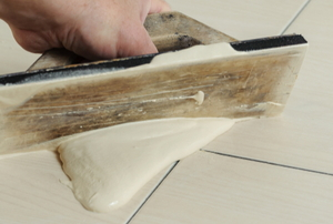 hand applying tile grout with a scraper