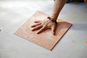 Hand on a square of porcelain tile