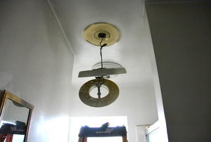 A bath ceiling heater half uninstalled.