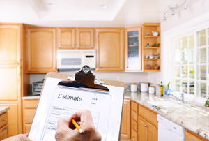 "A person in a kitchen holding a clipboard writing on a paper that says ""estimate."""