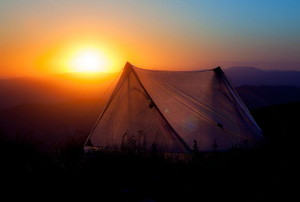 A tent against a sunrise.
