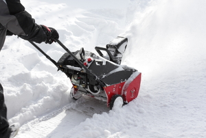 Man removing snow after storm with a snowblower.