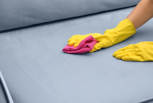 A woman cleans a stain on a couch.