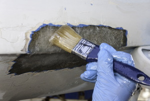 a hand in blue gloves holding a paint brush against a wall