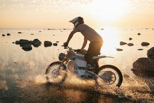 A man riding a dirt bike at sunset