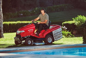 A man on a riding lawn mower.
