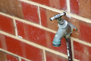 An outdoor faucet attached to a brick wall.